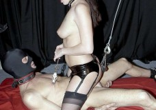 Chica con corsé juega con su esclavo