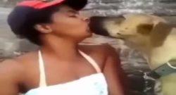 Perro dando besos con lengua a chica negra